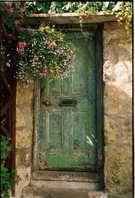 Cheerful hanging basket - like the subdued extravagence to one side of the distressed green door