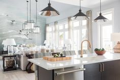 Opening on to the living room, the colors of both rooms blend beautifully as they rely on black, white and gray to support the decorating scheme. A wall mural of a vintage surfing scene can be seen from the kitchen.  | HGTV® Dream Home 2016