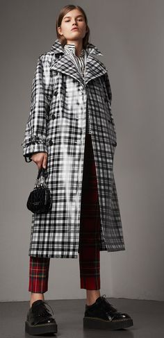 A high-gloss laminated Modern Scott tartan wool trench coat. The relaxed cut has an undulating storm shield and inverted box pleat at the back for volume. Mix your patterns to make the plaid pop.