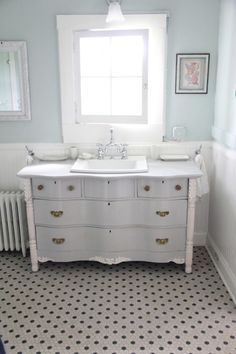 Benjamin Moore Palladian Blue on the walls, BM Coventry Gray on the vanity, and BM Mountain Peak White on the trim and wainscoating
