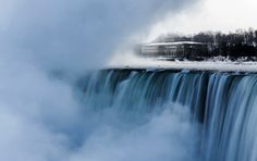 An old hydro building is seen behind Niagara Falls during sub-freezing temperatures
