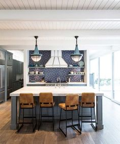 Gorgeous kitchen with navy cabinets and black splash.
