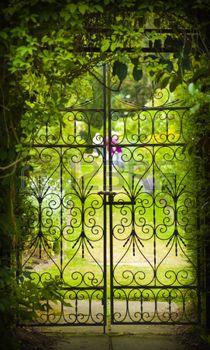 smeedijzer%3A+Een+poort+verbergt+een+groene%2C+bloemrijke+tuin+Stockfoto