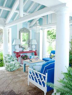 """The 1920s pavilion is """"full Florida style."""" Vintage seating — white faux bamboo and an armchair covered in Fig Leaf by Peter Dunham — are breezily mixed with a red Coleen & Company console that has carved elephant heads and trunks for legs and holds shell lamps from the Breakers in Palm Beach."""
