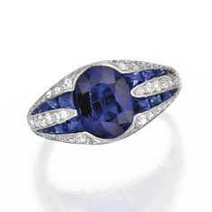 PLATINUM, SAPPHIRE AND DIAMOND RING. Centered by an oval-shaped sapphire weighing approximately 2.25 carats, flanked by 48 single-cut diamonds weighing approximately .45 carat and 16 French-cut sapphires, size 6½, circa 1925.
