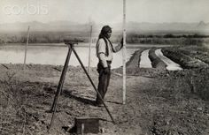 A North American Indian uses survey equipment near irrigation ditches. circa 1915.