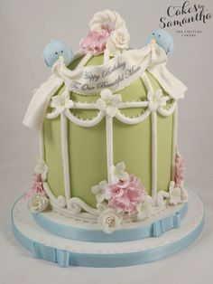 Birdcage cake with little blue birds holding the birthday banner.