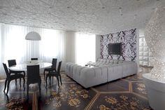 Este apartamento em Amsterdã, na Holanda, ganhou um projeto um tanto quanto inusitado. Assinado pelo arquiteto Marcel Wanders, o espaço conta com texturas em muitos elementos do décor, a exemplo do teto branco, que é nada minimalista. Se por um lado a sala é repleta de detalhes, a paleta de cores se mantém enxuta, centrada em branco, preto, marrom e bege. Atrás da televisão, um papel de parede elaborado contrasta com o piso, que exibe um rico trabalho de marchetaria.