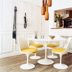 Yellow adds a touch of brightness to this dining space. #Eero #Saarinen