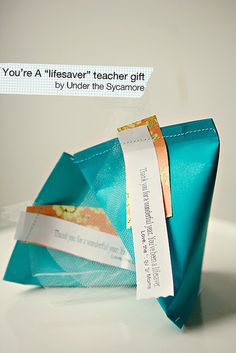"""DIY {You're a """"lifesaver"""" teacher gifts for Teacher Appreciation Week made with scrapbook paper and filled with Lifesavers candy} by Under the Sycamore Summer Gift Baskets, Teacher Gift Baskets, Teacher Treats, Teacher Gifts, Teacher Stuff, Back To School Teacher, Firefighter Gifts, Teacher Appreciation Week, Wraps"""