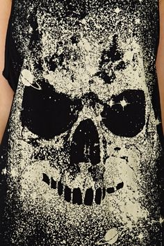 cut out skull shapes in contact paper + stick them to shirt + spray bleach in a spray bottle over black shirt