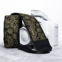 Your camera will look stunning with this black and gold metallic paisley strap. 100% cotton, lightly padded camera strap comes in your choice of two lengths, end styles and pocket options. Materials: