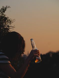 A girl holding a bottle of beer at sunset in silhouette