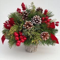 Centerpiece by Lipinoga Florist of Clarence, NY - Call for delivery throughout WNY: (716)759-6563 Shop online for Christmas Flowers, Plants and more including this elegant Christmas Centerpiece shown with berries, evergreens, pinecones, velvet ribbons and more: www.LipinogaFlorist.com