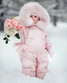 Little girl bundled up in pink snowsuit, so cute