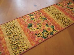 """Beautiful fall flowers are in this table runner. The colors are mainly orange yellow and gold. Bring color to your table this season. This would make a wonderful gift. This table runner is 14"""" x 47.5"""""""