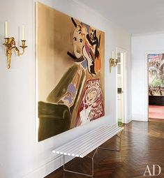A painting by Sophie von Hellermann is displayed above a white Harry Bertoia bench in the entrance hall | archdigest.com
