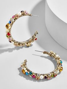 A new twist on an old favorite, these bejeweled hoop earrings are an effortless way to add sparkle to any outfit. Their embellished palette makes them a chic conversation piece at any party.