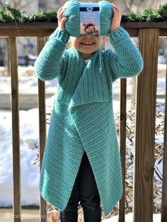 little girl holding a skein of yarn over her face wearing a blanket cardigan