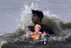 Mumbai, India: A man carries an idol of the Hindu elephant-headed god Ganesha, for immersing in the Arabian Sea during the Ganesh Chaturti festival