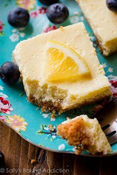 Creamy and tangy lemon bars made with Greek yogurt-- only 130 calories per lemon square! Easy recipe on sallysbakingaddiction.com