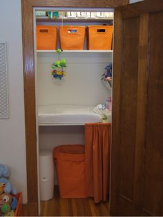 this is the closet/changing table idea we're looking at - build a shelf waist-height and have the cubes/storage beneath - and i love the quick-grab stuff hanging on the side!