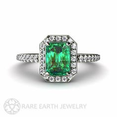 An absolutely gorgeous Emerald and diamond ring in Platinum. The center stone is a lovely lab grown Emerald weighing .85 carats and measuring 7x5mm.