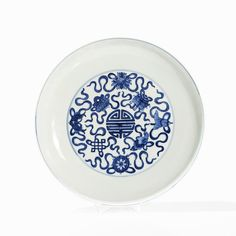 Porcelain dish with underglaze blue painting China, Qing dynasty (1644-1911). Elegant bowl on a narrow base rim. In the center the Shou character, surrounded by the eight Buddhist symbols of good luck among double circles The outer wall with a revolving décor of the eight Buddhist symbols of good luck. Base with the six-character Qianlong mark. 4.5 x 26 cm