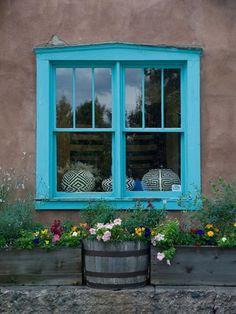 Paredes de adobe e jsnela azul de madeira e vidros. As flores fizeram a difetenca. Em Santa Fe, Novo Mexico, USA.  Fotografia: Krista Rossow.