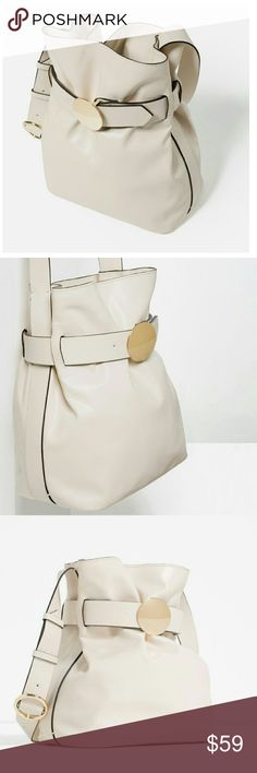 ZARA Brooch Clasp Bucket Bag Bucket Bag in ecru.  Gold tone hardware detail.  Adjustable shoulder strap with metallic buckle.  Lining and interior pocket.  Gathered closure.  H31x W27x D17 cm.  Outer 100% polyurethane. Zara Bags
