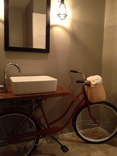 bike bathroom remodel- restored bike from the '60s, nantucket basket, custom plumbing, and counter top from restored floor boards.