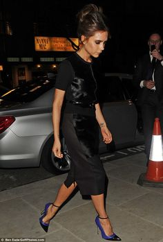 Victoria Beckham wearing black shift skirt boasting calf hair panels, short sleeved jumper and belt from her FW 2013 collection, along with Manolo Blahnik for Victoria Beckham heels.