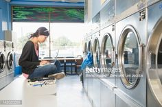 Stock Photo : Hispanic woman using laptop in self-service laundry facility