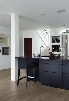 Alle skabs- og skuffeelementer i køkkenet har låger af mørkbejdset eg. Køkkenelementerne er fra Invita. Barstolen er fra Ikea. Køkkenbordpladen er lavet af sort granit med en speciel overfladebehandling, der giver den et mat og lidt læderagtigt look, og er designet, så den rager ud over skabs-elementerne.