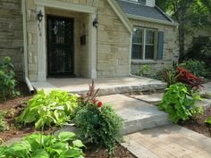 Front entryway landscaping and natural stone and paver patio and walkway by Norland Landscape Madison, WI