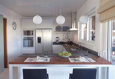 Balcão que divide cozinha da sala de jantar pode servir para refeições rápidas  Luminárias distribuídas sobre o balcão