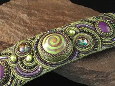 Hey, I found this really awesome Etsy listing at https://www.etsy.com/listing/202783747/bead-embroidered-cuff-purple-swirl