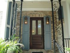Mahogany front door with beveled glass, Chicago brick exterior wall, cypress shutters and hand made Bevolo copper lanterns Modern Shutters, Modern Exterior Doors, House Shutters, Exterior Front Doors, Modern Farmhouse Exterior, Exterior Trim, Exterior Shutters, French Farmhouse, Exterior Design
