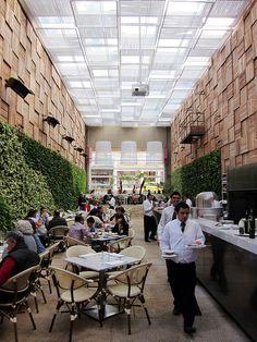 muros verdes artificiales, iluminación drámatica, maderas, el exterior en el interior, concepto invernadero... lámparas de jaula sobredimensionadas