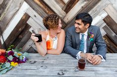 This fun and contemporary couple enjoy a beer at Geer Street Garden in Durham, North Carolina after their wedding ceremony. We love the fun colors this bride and groom incorporated their wedding day between the brides dress, the grooms tie and the grooms boutonnière. You can tell how comfortable this couple is in front of their photographer, MKM Photography. Wedding Planner -Paisley & Pearl Events.