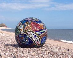 Floating glass mosaic sphere by Sue Smith, member of the Contemporary Glass Society. She uses scrap stained glass where possible which Sue buys from leaded glass artists, plus new glass. This is mosaic-ed onto a polystyrene ball which can be displayed on water or land.