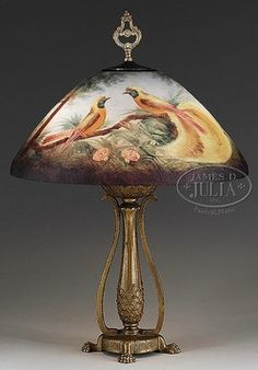 """lighting, Wisconsin, Moe Bridges exotic bird table lamp. Nice Moe Bridges table lamp is reverse painted with two exotic birds with bright yellow plumage resting on a branch. The remainder of the shade is decorated with tall trees, blue and pink flowers and light blue sky. The shade is signed on the bottom edge """"Moe Bridges"""" Circa 1901-1930"""