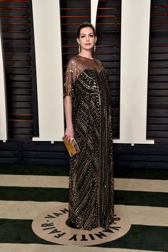 Anne Hathaway showed off her baby bump in her shimmering gown.