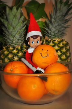 Elf on a Shelf idea - in a bowl of oranges (writes happy face on the orange)