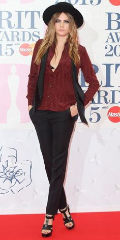 Cara Delevingne in black pants, a red blouse, and a black hat at Brit Awards 2015