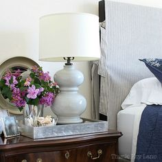 Headboard Slipcover- see how to make a simple headboard slipcover using ticking fabric for an updated French cottage style bedroom.