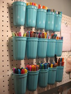 """plain plastic cups from the grocery store. we drill 2 holes in them and use zip ties through the peg board to keep them in place!"" -Great for a kid's room idea... maybe find a way to make the cups removable so they can bring it to the table...."