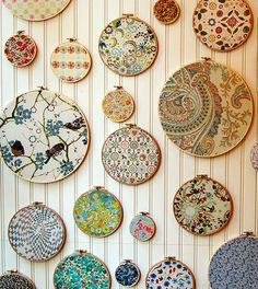Embroidery hoops & well-chosen fabric swatches - great idea for a sewing or crafting room wall.