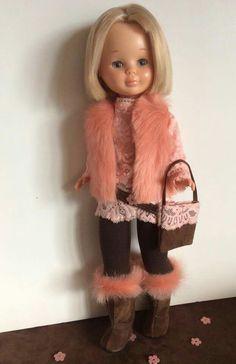 Nancy con diseño El Costurero de Chus. Blusa de encaje rosa, leggings marrónes, chaleco y botas de pelo.