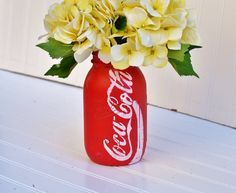 Mason jar vase painted to look like coco cola can.